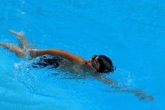 A criança asiática nada na piscina - o estilo do rastejamento dianteiro com poder scissor o pontapé Fotografia de Stock