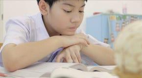 Criança asiática no uniforme do estudante para fazer em casa trabalhos de casa fotos de stock royalty free
