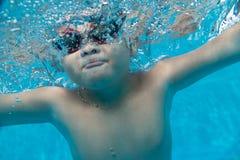 Criança asiática nova feliz com os óculos de proteção da nadada subaquáticos Foto de Stock