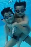 Criança asiática nova feliz com os óculos de proteção da nadada subaquáticos Fotos de Stock Royalty Free