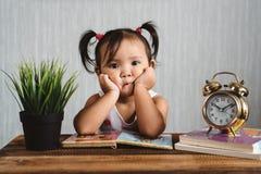 Criança asiática pequena bonito do bebê que faz cara aborrecida quando livros de leitura com despertador imagens de stock