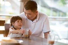 Criança asiática pequena que bebe no café imagem de stock