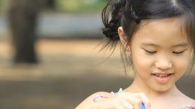 Criança asiática pequena que tem o divertimento que faz bolhas video estoque