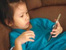 Criança asiática pequena que usa o smartphone no concentrado do olhar do sofá-cama para satisfazer Usar o smartphone para criança fotografia de stock royalty free