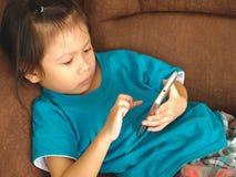 Criança asiática pequena que usa o smartphone no concentrado do olhar do sofá-cama para satisfazer Usar o smartphone para criança imagens de stock