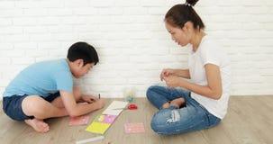 Criança asiática que aprende a dobrar o origâmi do papel japonês com mãe vídeos de arquivo