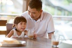 Criança asiática que bebe no café imagens de stock royalty free