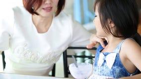 A criança asiática que come uma nata do gelo com minha mãe relaxa dentro o tempo video estoque