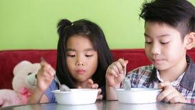 A criança asiática que come uma nata do gelo relaxa dentro o tempo video estoque