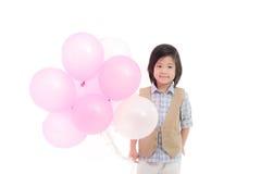 Criança asiática que guarda balões cor-de-rosa e brancos Foto de Stock