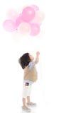 Criança asiática que guarda balões cor-de-rosa e brancos Foto de Stock Royalty Free