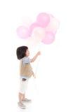 Criança asiática que guarda balões cor-de-rosa e brancos Imagens de Stock