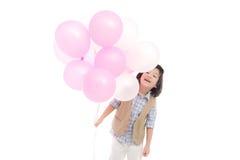 Criança asiática que guarda balões cor-de-rosa e brancos Imagem de Stock