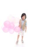 Criança asiática que guarda balões cor-de-rosa e brancos Fotografia de Stock Royalty Free
