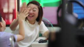 Criança asiática que olha o computador na biblioteca com seu professor na escola primária filme
