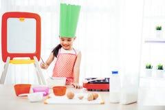A criança asiática que tem o divertimento com cozimento e preparação da massa, coze cookies na cozinha Foto de Stock Royalty Free