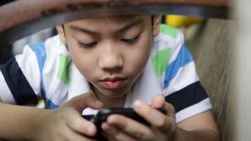 Criança asiática que usa um telefone celular digital ao encontrar-se para baixo no sofá em casa filme