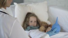 Criança assustado que olha o bulbo do aperto na mão dos doutores com medo nos olhos, medicina video estoque
