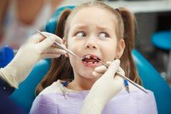A criança assustado senta-se na cadeira do dentista com boca aberta imagem de stock royalty free