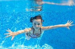 A criança ativa feliz nada debaixo d'água na associação imagem de stock