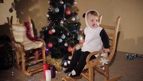 A criança balança em uma cadeira de balanço na perspectiva de uma árvore e das velas de Natal Modo do Natal vídeos de arquivo