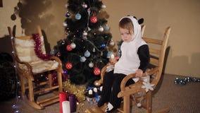 A criança balança em uma cadeira de balanço na perspectiva de uma árvore e das velas de Natal Modo do Natal video estoque