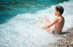 A criança banha a praia Zanjic Montenegro de Lustica do mar de Adriatik da ressaca das ondas imagem de stock