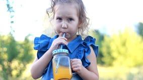 A criança bebe fresco alaranjado no verão Retrato de uma menina que aprecie batidos através de um tubo vídeos de arquivo