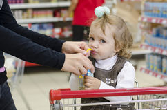 Uma criança bebe o suco na loja Fotografia de Stock