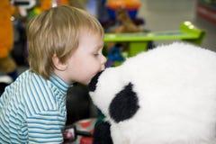 A criança beija um brinquedo Fotos de Stock