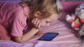 Criança bonita com cabelo louro, em uma camisa cor-de-rosa que encontra-se na ucha e que olha desenhos animados em seu telefone c filme