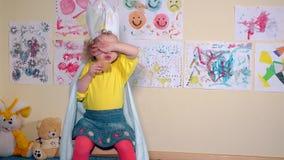 Criança bonita da menina com coroa de papel que come cookies e que acena a mão video estoque