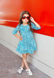 Criança bonita da menina que veste um vestido e óculos de sol do leopardo sobre o vermelho colorido Imagem de Stock