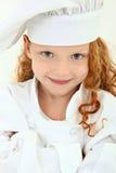 Criança bonita da rapariga no uniforme e no chapéu do cozinheiro chefe fotos de stock