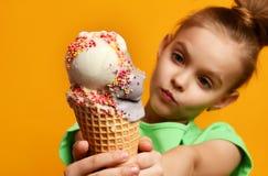 Criança bonita do bebê que come lambendo o gelado da banana e da morango no cone dos waffles Imagens de Stock