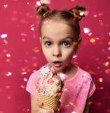 Criança bonita do bebê que mantém o gelado no cone dos waffles com exibição da framboesa surpreendido Fotos de Stock