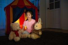 Criança bonita feliz que joga o jogo com urso de peluche Fotografia de Stock