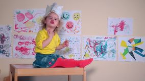 Criança bonita irritada que come a cookie que senta-se na tabela contra pinturas na parede video estoque