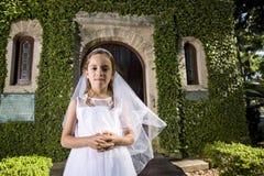Criança bonita na porta exterior da capela do vestido branco Imagem de Stock Royalty Free