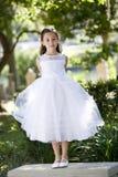 Criança bonita no vestido branco no banco de parque Imagem de Stock Royalty Free