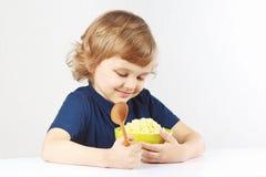 Criança bonita que abraça a bacia de favorito do cereal do painço Fotos de Stock Royalty Free