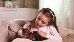 Criança bonita que afaga um cachorrinho Toy Terrier filme