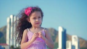 Criança bonita que faz a forma do coração com mãos no por do sol, menina bonito que guarda um símbolo do amor, sorrindo docemente filme