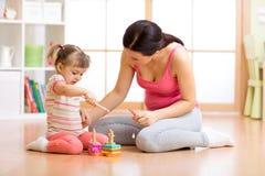Criança bonita que joga com os brinquedos com mãe feliz dentro fotografia de stock
