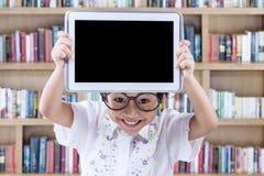 Criança bonita que mostra a tabuleta na biblioteca Imagens de Stock Royalty Free
