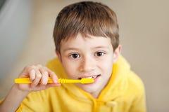 Criança bonita que prepara-se para escovar seus dentes que vestem roupões amarelos closeup imagem de stock royalty free