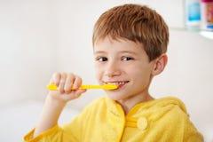 Criança bonita que prepara-se para escovar seus dentes que vestem roupões amarelos closeup Fotos de Stock