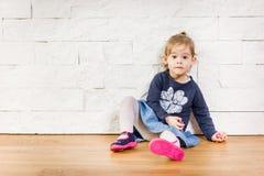Criança bonita que senta-se contra a parede Fotos de Stock