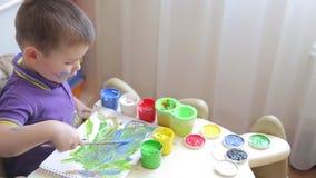 A criança bonita tira com pinturas coloridas ao sentar-se na tabela vídeos de arquivo
