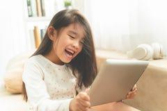 Criança bonito asiática que joga jogos com uma tabuleta e que sorri quando foto de stock royalty free